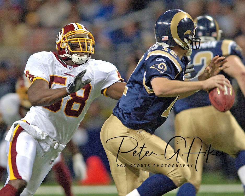 Washington Redskins linebacker Chris Clemons (L) pressures St. Louis Rams quarterback Ryan Fitzpatrick (R) in the first half, at the Edward Jones Dome in St. Louis, Missouri, December 4, 2005.  The Redskins beat the Rams 24-9.