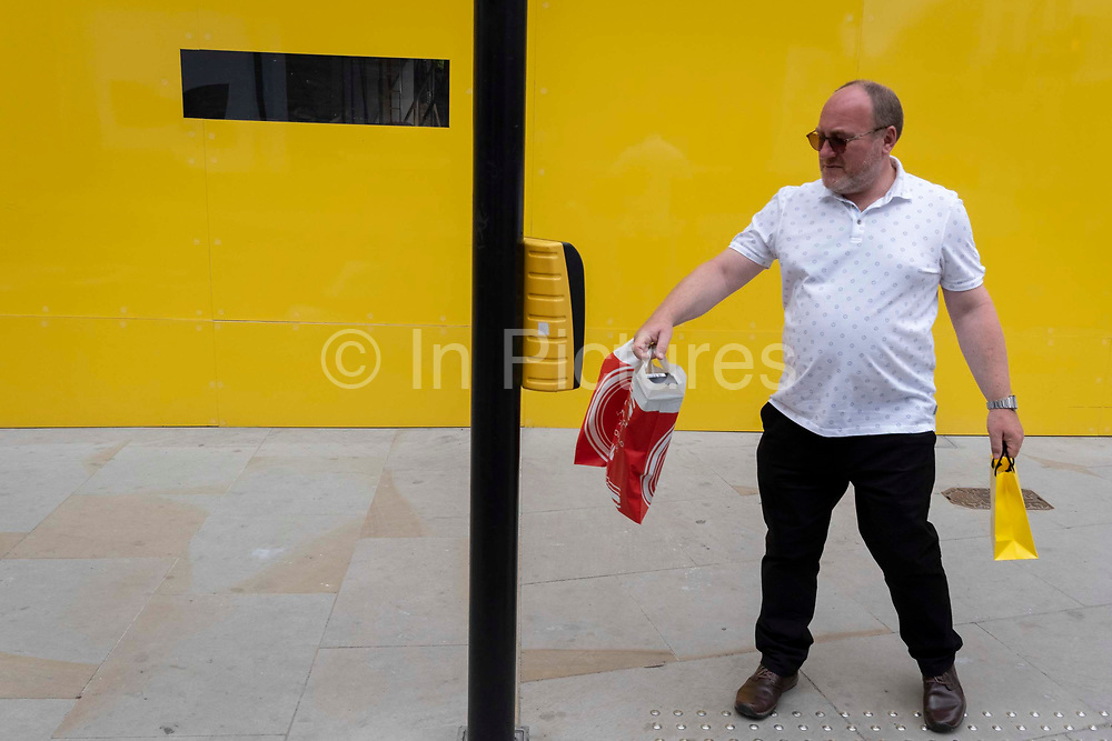 A male shopper reaches to touch the Stop button for the traffic to stop on Brook Street in Mayfair, on 12th July 2021, in London, England.
