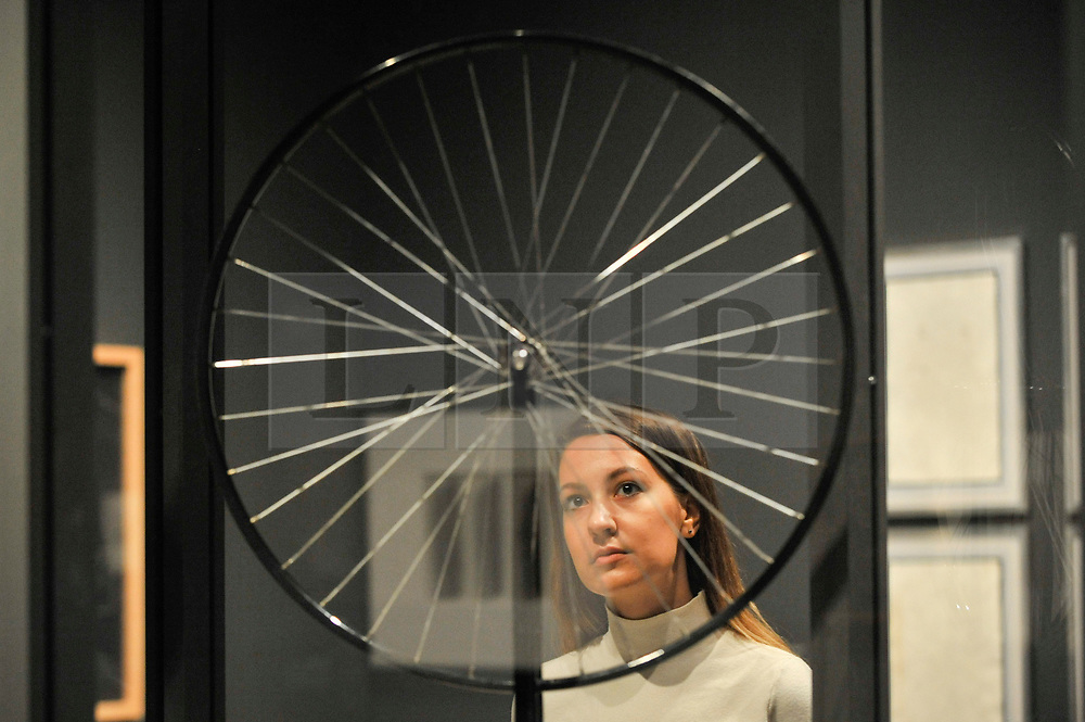 "© Licensed to London News Pictures. 03/10/2017. London, UK.  A staff member views ""Bicycle Wheel"", 1913, 1964 edition, by Michel Duchamp at the preview of ""Dali / Duchamp"", a new exhibition of works by Salvador Dali and Michel Duchamp taking place at the Royal Academy of Arts in Piccadilly.  Over 80 artworks in different media are on display from 7 October to 3 January 2018.   Photo credit : Stephen Chung/LNP"