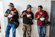 "23 FEBRUARY 2014 - NAKHON RATCHASIMA (KORAT), NAKHON RATCHASIMA, THAILAND: Men eat their lunch in the hallway of their meeting venue during the Red Shirt meeting in Korat. The United front of Democracy against Dictator (UDD or Red Shirts), which supports the elected government of Yingluck Shinawatra, staged the ""UDD's Sounding of the Battle Drums"" rally in Nakhon Ratchasima (Korat) to counter the anti-government protests that have gripped Bangkok since November. Around 4,000 of UDD's regional and provincial coordinators along with the organization's core members met at Liptapunlop Hall inside His Majesty the King's 80th Birthday Anniversary Sports Complex in Korat to discuss the organization's objectives and tactics against anti-government protestors, which the UDD says ""seek to destroy the country's democracy."" The UDD leadersa announced that they will march to Bangkok and demonstrate against anti-government protests led by Suthep Thaugsuban.   PHOTO BY JACK KURTZ"
