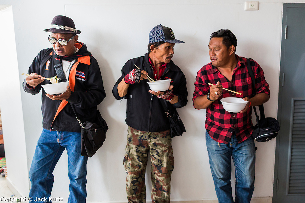 """23 FEBRUARY 2014 - NAKHON RATCHASIMA (KORAT), NAKHON RATCHASIMA, THAILAND: Men eat their lunch in the hallway of their meeting venue during the Red Shirt meeting in Korat. The United front of Democracy against Dictator (UDD or Red Shirts), which supports the elected government of Yingluck Shinawatra, staged the """"UDD's Sounding of the Battle Drums"""" rally in Nakhon Ratchasima (Korat) to counter the anti-government protests that have gripped Bangkok since November. Around 4,000 of UDD's regional and provincial coordinators along with the organization's core members met at Liptapunlop Hall inside His Majesty the King's 80th Birthday Anniversary Sports Complex in Korat to discuss the organization's objectives and tactics against anti-government protestors, which the UDD says """"seek to destroy the country's democracy."""" The UDD leadersa announced that they will march to Bangkok and demonstrate against anti-government protests led by Suthep Thaugsuban.   PHOTO BY JACK KURTZ"""