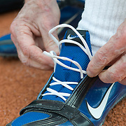 Date: 6/27/09.Desk: NAT.Slug: aging$500.Assign Id: 30081997A..Thomas Rice, 81, of the Philadelphia Masters Track & Field Club, ties on his spikes before competing in the triple jump at the 2009 USATF (USA Track & Field) East Region Masters Track & Field Championships at East Stroudsburg University in East Stroudsburg, Pennsylvania on June 27, 2009...Photo by Angela Jimenez for The New York Times .photographer contact 917-586-0916