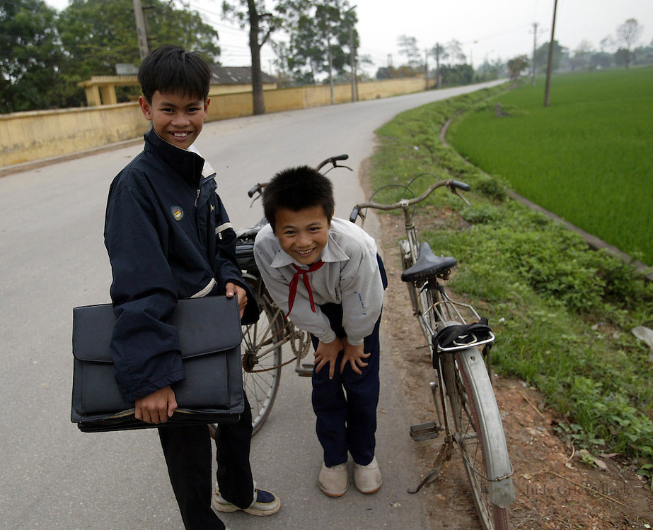 """School children in their uniforms stop to greet an American visitor on a country road near the """"Painting Village""""  outside Hanoi."""