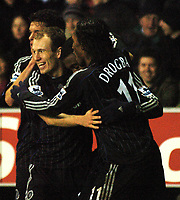 Photo: Paul Greenwood.<br />Wigan Athletic v Chelsea. The Barclays Premiership. 23/12/2006. Chelesa's Salomon Kalou, hidden, is mobbed by a smiling Arjen Robben, left and Didier Drogba.
