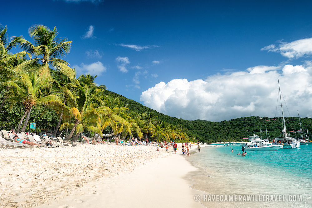 Visitors enjoy the white sandy beach at White Bay on Jost Van Dyke in the British Virgin Islands. The beach is famous for a string of bars serving tropical drinks, most famously the Soggy Dollar Bar.