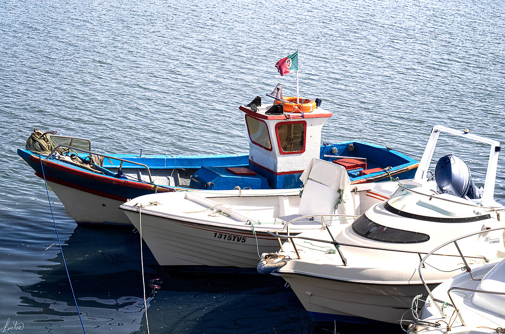 A vintage boat with a Portuguese flag alongside some modern boats in the Gilão river in Tavira, Portugal.