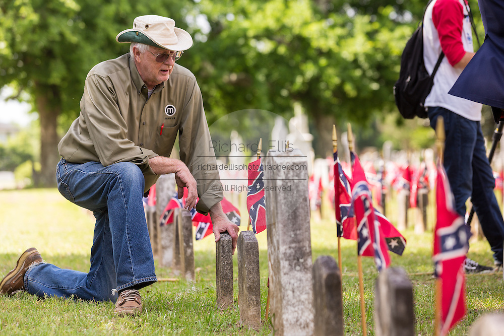 A descendant of Civil War soldiers kneels at the tombs of Confederate soldiers killed in the American Civil War during a ceremony marking Confederate Memorial Day at Magnolia Cemetery April 10, 2014 in Charleston, SC. Confederate Memorial Day honors the approximately 258,000 Confederate soldiers that died in the American Civil War.