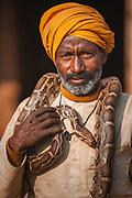 A snake charmer with a python wrapped around his shoulders, Dasaswamedh Ghat, River Ganges, Varanasi, India