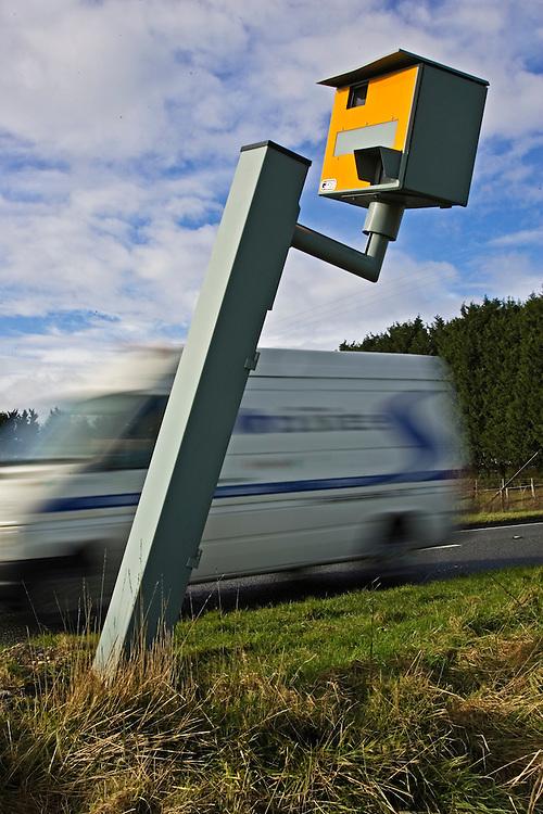 Traffic passes vandalised Gatso speed camera on A40, Oxfordshire, England, United Kingdom