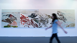 "© Licensed to London News Pictures. 19/05/2016. London, UK. A visitor walks in front of Kuo Chih-Hung's ""Mountain"" series.  Art16 opens at Olympia, in west London.  Now in its fourth edition, the fair brings together over 100 galleries from more than 30 countries showcasing a diverse cross-section of work by contemporary artists from around the world for buyers and art enthusiasts to visit. Photo credit : Stephen Chung/LNP"