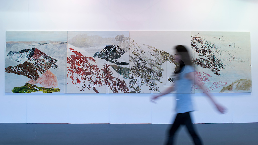 """© Licensed to London News Pictures. 19/05/2016. London, UK. A visitor walks in front of Kuo Chih-Hung's """"Mountain"""" series.  Art16 opens at Olympia, in west London.  Now in its fourth edition, the fair brings together over 100 galleries from more than 30 countries showcasing a diverse cross-section of work by contemporary artists from around the world for buyers and art enthusiasts to visit. Photo credit : Stephen Chung/LNP"""
