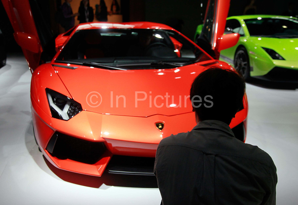 A man looks at Lamborghini SpA sports vehicles during the the China ( Guangzhou) International Automobile Exhibition in Guangzhou, Guangdong Province, China, on Monday, Nov. 21, 2011. Despite signs of slowing, China remains the largest and fastest growing market for international car makers, especially in the luxury sector.