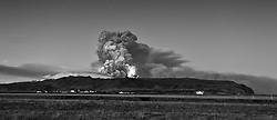 Volcanic eruption, Eyjafjallajokull, Iceland. Farms are standing below the exploding mountain