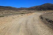 Dirt road crossing dry barren mountain landscape near Paraja, Fuerteventura, Canary Islands, Spain