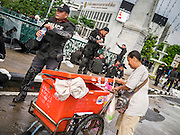 23 NOVEMBER 2012 - BANGKOK, THAILAND: A Thai riot police buys water from a vendor during training for a large anti-government protest in Bangkok Friday. Thai authorities have imposed the Internal Security Act (ISA), that enables police to call on the army if needed to keep order, and placed thousands of riot police in the streets around Government House in anticipation of a large anti-government protest Saturday. The group sponsoring the protest, Pitak Siam, said up to 500,000 people could turn out to protest against the government. They are protesting against corruption in the current government and the government's unwillingness to arrest or pursue fugitive former Prime Minister Thaksin Shinawatra, deposed in 2006 coup and later convicted on corruption charges. The current Thai Prime Minister is Yingluck Shinawatra, Thaksin's sister.       PHOTO BY JACK KURTZ