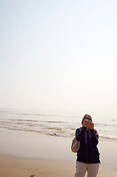 Woman taking a photograph on a beach
