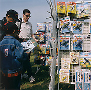 Young and older aviation enthusiasts look through a rack of modelling kits during an airshow at Biggin Hill in Kent, southern England. Packets of scaled models of all types - in particular, British Spitfires and Mustangs) are on display for the buyer to browse during the hours before the flying displays commence at this small airfield north of London.
