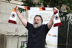 Russell Crowe is pictured holding up a scarf of the AS Roma football team during a photocall for Gladiator Live in Concert in Rome