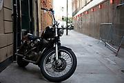 Vintage motorcycle in a back street alleyway in Soho, London, United Kingdom.