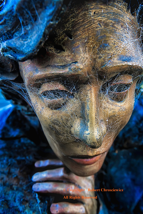 Far Away Eyes: A close-up of a painted metal statue of a person deep in thought, with cobwebs covering the eyes, Gardiner Oregon USA.