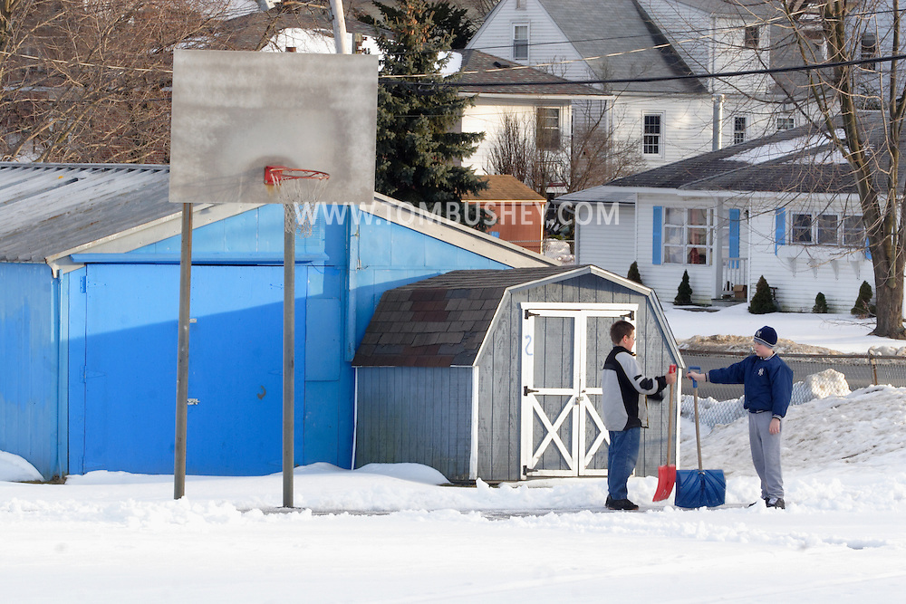 Middletown, New York - Two boys with snow shovels talk after clearing snow off part of a basketball court on Feb. 21, 2007.