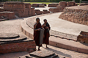 Buddhist monks praying as they walk around Dharmarajika Stupa at Sarnath ruins near Varanasi, Benares, Northern India