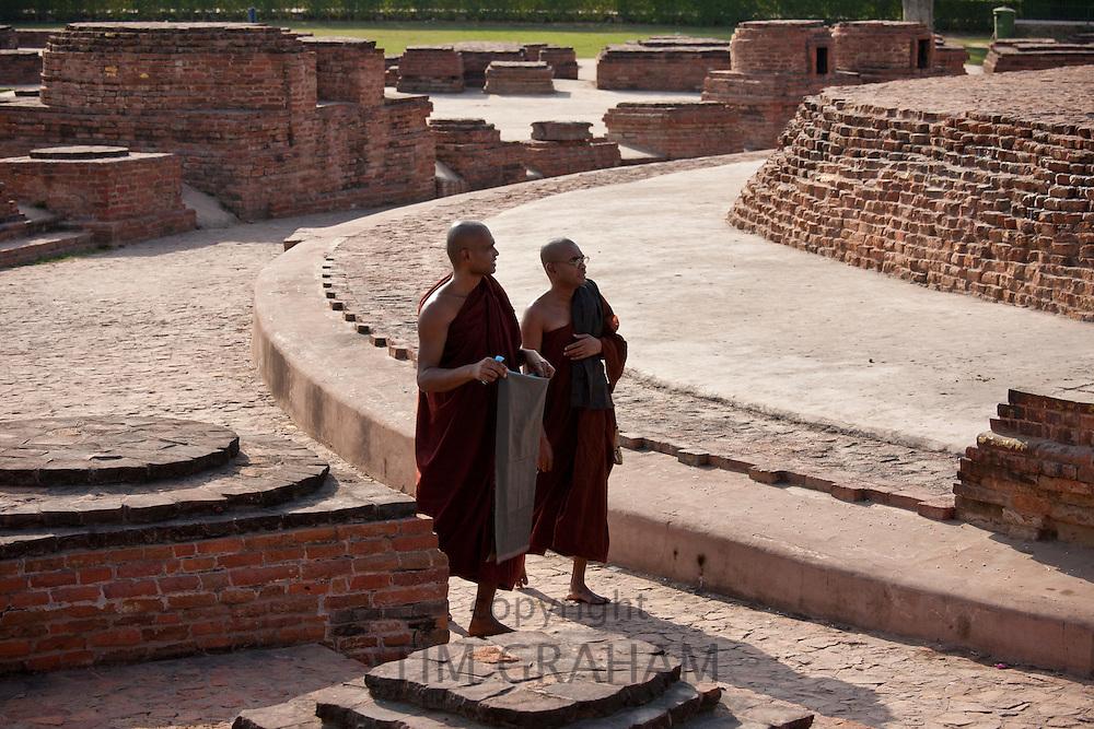 Buddhist monks praying as they walk around Dharmarajika Stupa at Sarnath ruins near Varanasi, Benares, Northern India