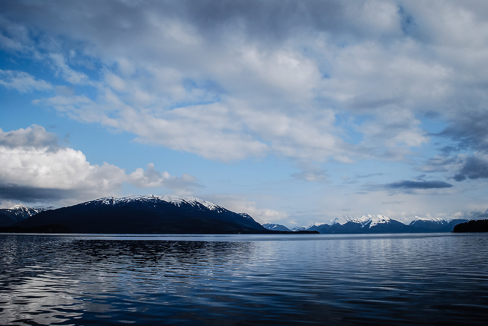This calm Alaskan landscape is a nice wide angle view of nature in Alaska with the mountains in the distance and the calm ocean waters and puffy clouds in the sky.
