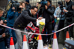 © Licensed to London News Pictures. 23/03/2017. London, UK. A member of the public lays flowers on Westminster Bridge, the day after a lone terrorist killed 4 people and injured several more, in an attack using a car and a knife. The attacker managed to gain entry to the grounds of the Houses of Parliament, killing one police officer. Photo credit: Ben Cawthra/LNP