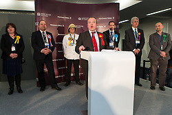 © Licensed to London News Pictures . 14/02/2014 . Manchester , UK . Labour Party candidate MIKE KANE (front centre) delivers his victory speech as other candidates - L-R Mary Di Mauro (Liberal Democrats) , Eddy O'Sullivan (BNP) , Captain Chaplington-Smythe (Monster Raving Loony Party) , Reverend Daniel Critchlow (Conservatives) , John Bickley (UKIP) and Nigel Woodcock (Greeen Party) - stand behind  . The count for the Wythenshawe and Sale East by-election , at Manchester Central this evening . Photo credit : Joel Goodman/LNP