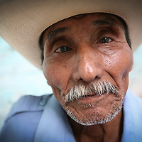 An elderly man leaves the El Jabalí coop after being paid for cutting coffee. Cooperativa El Jabali is a certified Fairtrade coffee producer based in El Salvador.