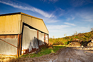 Corrugated barn with rust and damage in Rackham, West Sussex, England , UK
