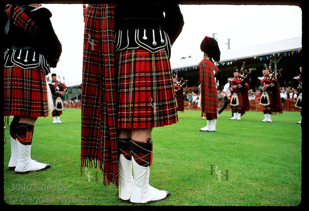 Spats gleaming, pipe band circles around its pipe major at the Highland Games; July, Inverness. Scotland