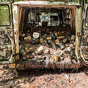 An old van in the Old Car City junkyard in Georgia is filled with hundreds of oil cans all piled up.