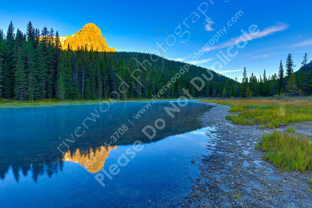 Aplenglow on the mountain peaks surrounding Upper Waterfowl Lake at Sunrise with the mountains reflected the glassy calm waters of the lake.<br /> <br /> ©2015, Sean Phillips<br /> http://www.RiverwoodPhotography.com