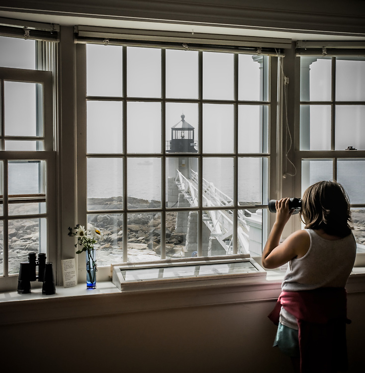 Peering through the fog, a young visitor keeps watch, as many have done before, out from Marshall Point Light station.