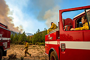 From left: Cal Fire HealdsburgÕs Daniel Frazee, Charles Schindler and Kassidy Harms watch as helicopters dump water down to the Kincade Fire off of Pine Flat Road on Friday, Oct. 25, 2019, east outside of Geyserville, Calif.