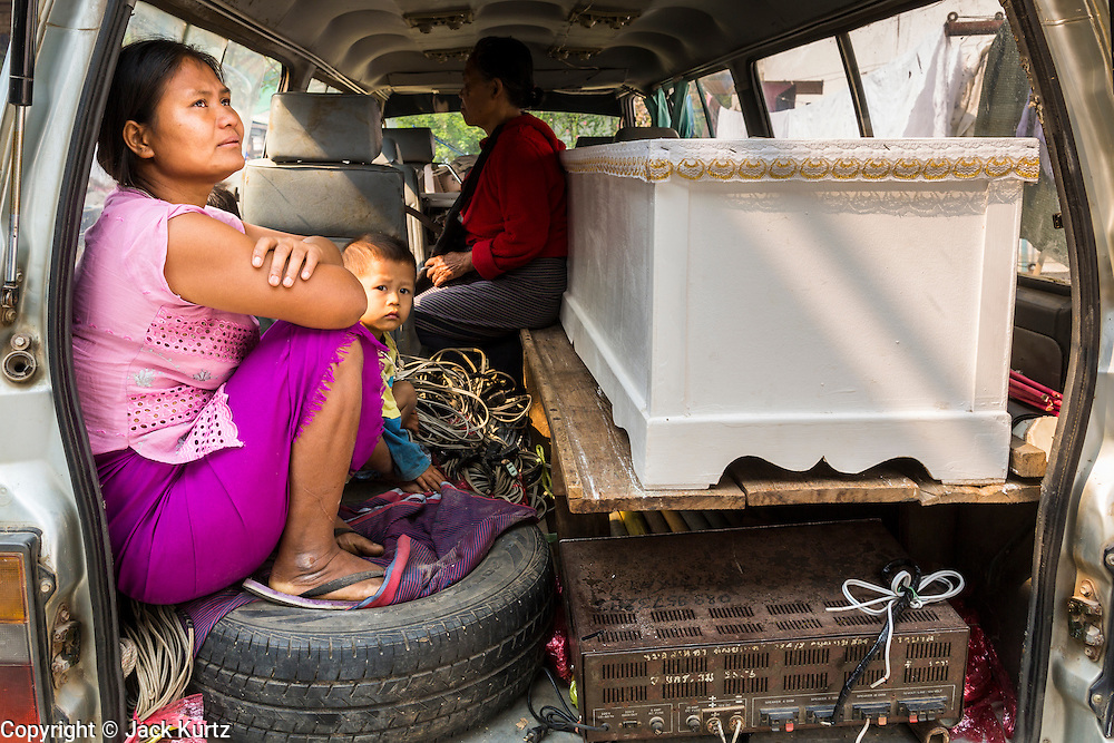 05 MARCH 2014 - MAE SOT, TAK, THAILAND: A woman sits next to her husband's coffin in the hearse taking them home after he died at the Mae Tao Clinic. The Mae Tao Clinic provides  healthcare to over 150,000 displaced Burmese per year and is the leading healthcare provider for Burmese along the Thai-Myanmar border. Reforms in Myanmar have alllowed NGOs to operate in Myanmar, as a result many NGOs are shifting resources to operations to Myanmar, leaving Burmese migrants and refugees in Thailand vulnerable.     PHOTO BY JACK KURTZ