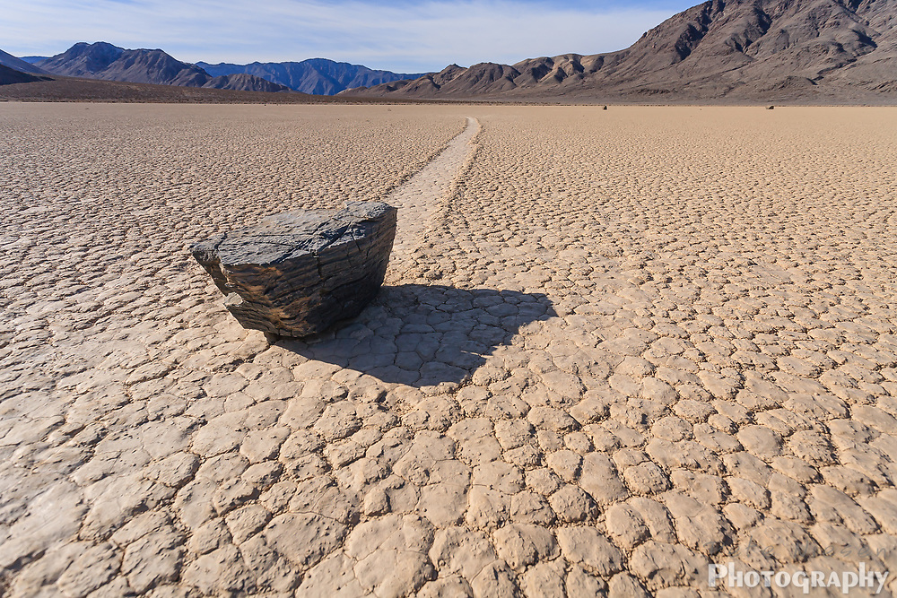 Boulder rock leaves a mysterious trail in cracked desert mud at the Race Track in Death Valley national Park