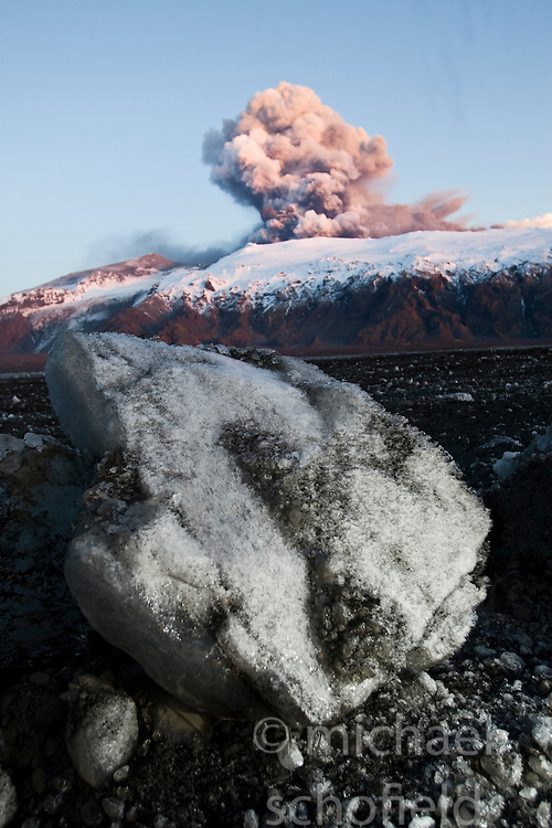Chunks of ice from a glacial flood triggered by a volcanic eruption lie in front of the Eyjafjallajoekull erupting volcano in Iceland. .©2010 Michael Schofield. All Rights Reserved.