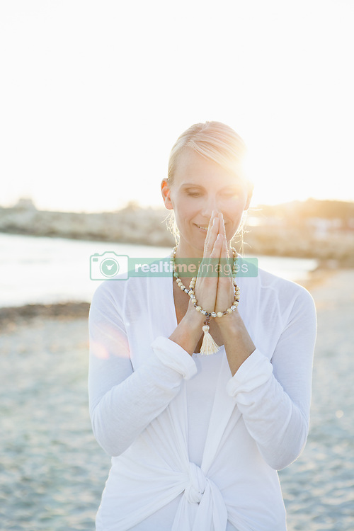 March 17, 2014 - Woman in yoga prayer pose on the beach (Credit Image: © Image Source/Image Source/ZUMAPRESS.com)