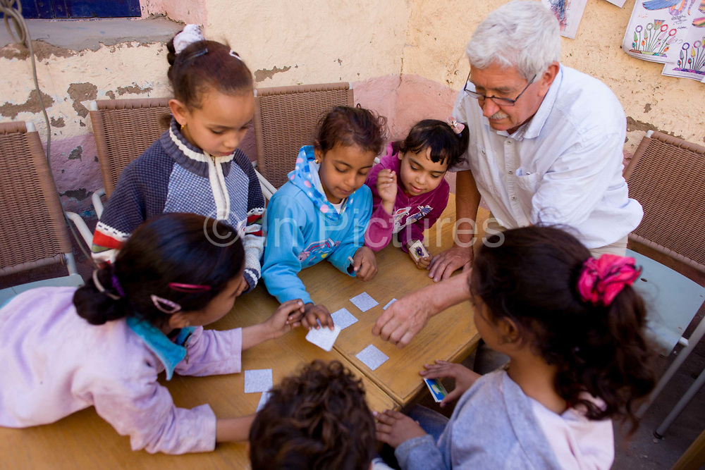 Local children get help with playing memory card games from a Belgian teaching volunteer at the American-sponsored Theban Mapping Project Library on the West Bank of Luxor, Nile Valley, Egypt. The Theban Mapping Project's goal is to enable local people to have a place where they can read and learn as state schools are under-resourced, lacking basic teaching aides such as books. The organisation is run by American Egyptologist Dr Kent Weeks who is committed to the original goal of accurately documenting the archaeological heritage of Thebes. (Photo by Richard Baker / In Pictures via Getty Image).