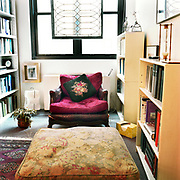 An old wood and leather chair with bright red pillows in it and a floral print pillow for back support, in front of two windows, a stained glass window hanging in front of the windows, bookcases on both sides and an hourglass sitting on top of the right foreground case. There is a floral print footrest in the foreground.
