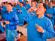 """09 FEBRUARY 2014 - HAT YAI, SONGKHLA, THAILAND: Men eat goat liver and drink Chinese rice wine in the Chao Mae Tubtim Shrine (Ruby Goddess Shrine) on 108 Hainanese Ancestors Memorial Day in Hat Yai, Songkhla, Thailand. Hainanese communities around the world celebrate """"108 Hainanese Ancestors Memorial Day."""" The day honors the time when 109 Hainanese villagers fleeing life in Hainan (an island off of the southwest coast of China, near Vietnam) washed up in what is now Vietnam and were killed by Vietnamese authorities because authorities thought they were pirates. The Vietnamese built a temple on the site and named it """"Zhao Yin Ying Lie."""" Many Vietnamese fisherman credit prayers at the temple to saving their lives during violent storms and now """"108 Hainanese Ancestors Memorial Day"""" is celebrated in Hainanese communities around the world. Hat Yai, the economic center of southern Thailand has a large Hainanese population.    PHOTO BY JACK KURTZ"""