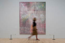 """© Licensed to London News Pictures. 30/05/2019. LONDON, UK. A staff member poses next to """"Raining Down South"""", 1968, by Frank Bowling at a preview of works by artist Frank Bowling (born in Guyana in 1934).  The retrospective exhibition spans his six-decade career and takes place 31 May to 26 August 2019 at Tate Britain.  Photo credit: Stephen Chung/LNP"""
