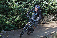 """Unknown mountain bike rider descending fast flowing red section, """"The 8"""" red track, Gisburn Forest"""