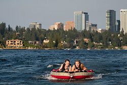 United States, Washington, Bellevue. Two teenage girls tubing, or biscuiting, behind a motorboat on Lake Washington with Bellevue skyline.  MR