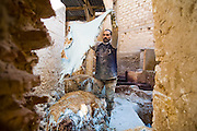 A worker at the Berber leather tannery in Fes El-Bali, Morocco, throws sheep skin leathers into a pile. They are coated in lime to make the hair easier to remove.