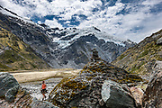 Glacier-clad Mt Edward (2620m) rises above a tramper in Dart Valley during a spectacular 20km round trip day hike from Dart Hut to Cascade Saddle, in Mount Aspiring National Park, Otago region, South Island of New Zealand.