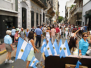 """Buy an Argentine flag and admire well-preserved old buildings at a street fair in San Telmo (""""Saint Pedro González Telmo""""), the oldest historic neighborhood (barrio) in the heart of Buenos Aires, Argentina, South America."""
